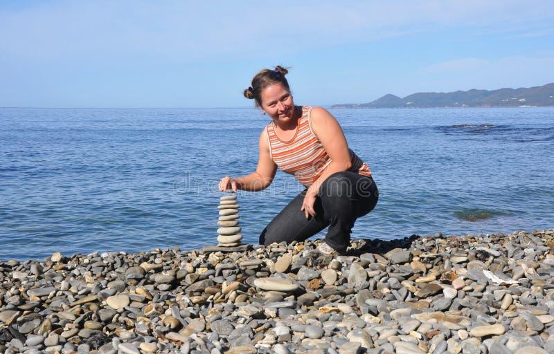 Молодая женщина собирает на пляже пирамиду с камешками. Черноморское побережье Кавказа, Россия стоковые изображения