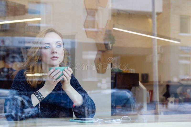 Молодая женщина со светлыми волосами и голубыми глазами выпивает кофе в кафе за окном со смартфоном на таблице стоковая фотография