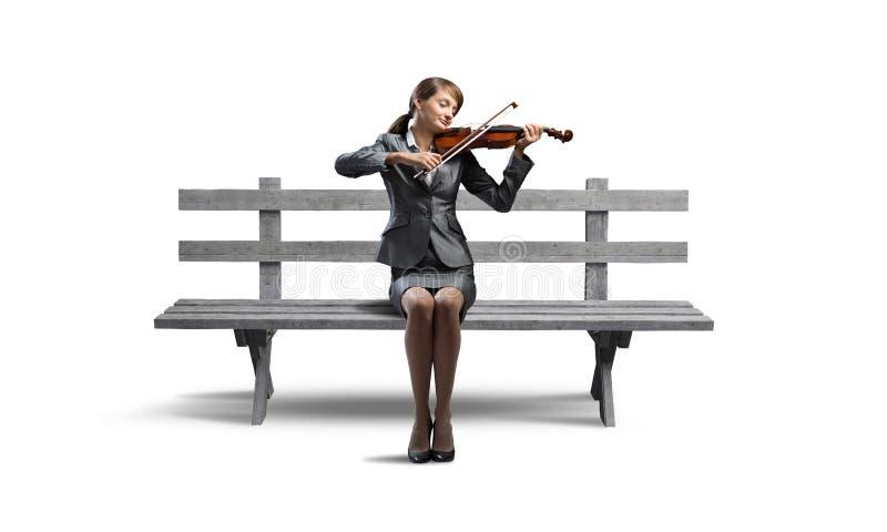Молодая женщина со скрипкой на деревянной скамье стоковые изображения