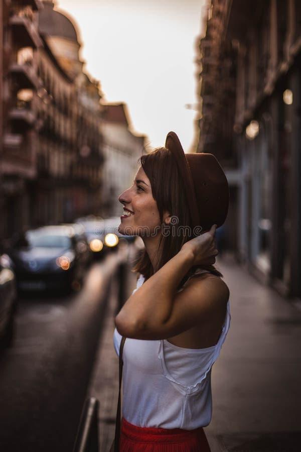 Молодая женщина со шляпой наслаждаясь туризмом на улице на заходе солнца в Мадриде, Испании стоковое изображение