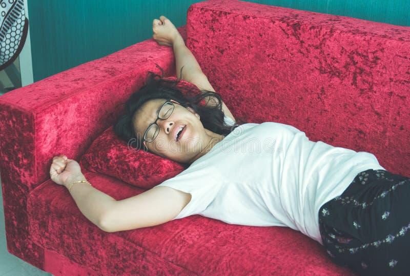 Молодая женщина спать на софе дома стоковые фото