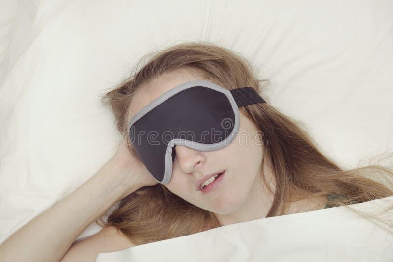 Молодая женщина спит в маске для сна Релаксация стоковое изображение rf