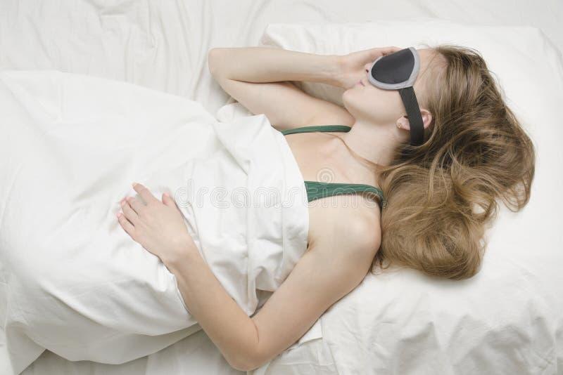 Молодая женщина спит в маске для сна Релаксация стоковое фото rf