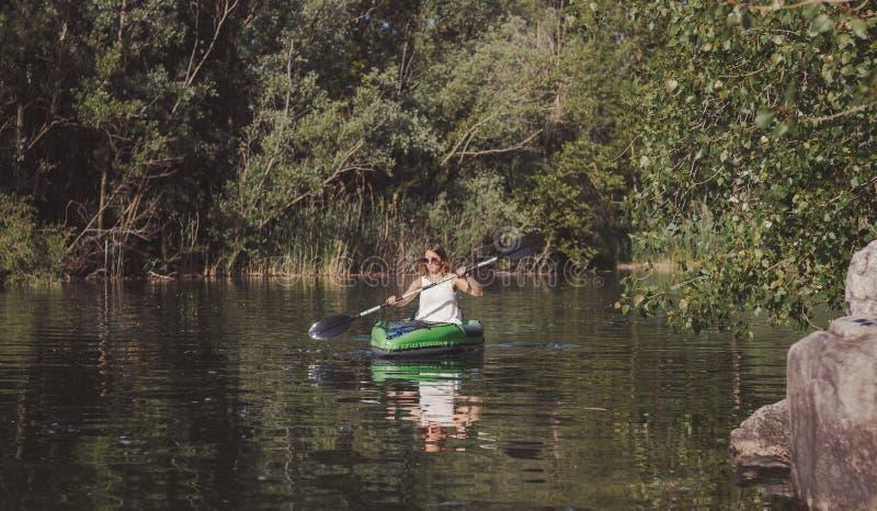 Молодая женщина сплавляясь на каяке на озере стоковые изображения