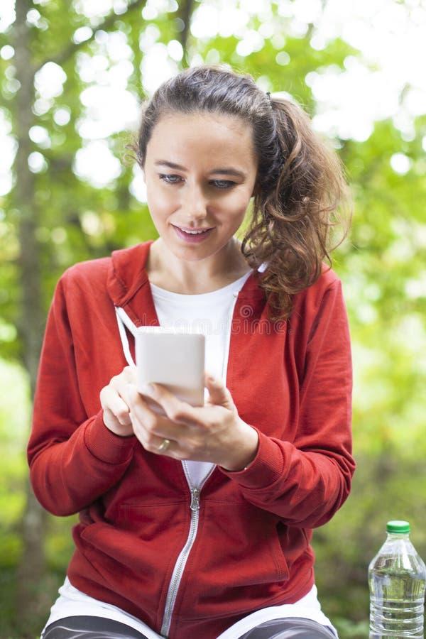 Молодая женщина спортсмена используя мобильный телефон после на открытом воздухе идущей разминки стоковое фото rf