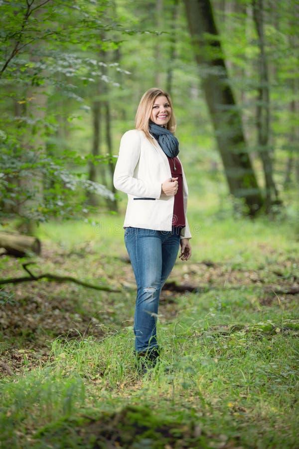 Молодая женщина стоит в зеленом лесу стоковые изображения rf