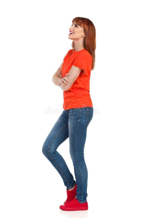 Молодая женщина стоит с пересеченными оружиями, смотрящ отсутствующей и говорить Взгляд со стороны стоковое фото
