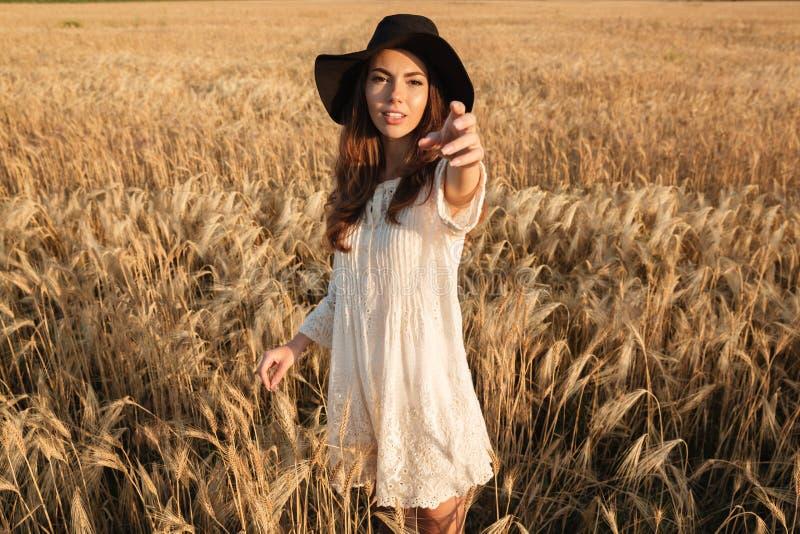 Молодая женщина стоя в поле вызывает вас стоковые изображения rf