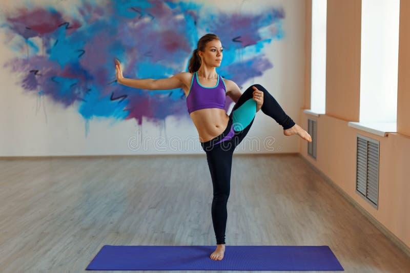Молодая женщина стоя в представлении йоги внутри помещения Здоровый уклад жизни стоковое изображение rf