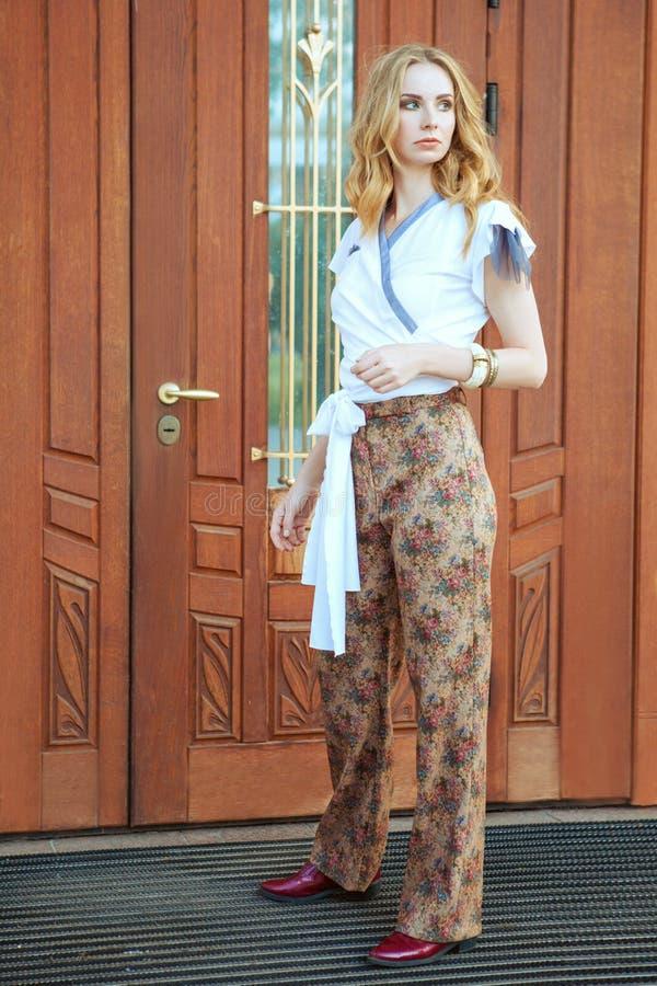 Молодая женщина стоя на двери стоковые фото