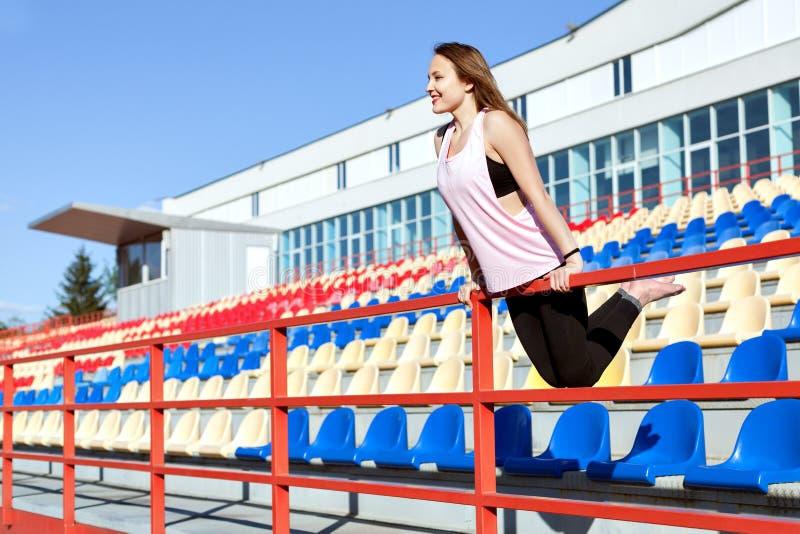 Молодая женщина стоя на подиуме стадиона стоковое фото rf