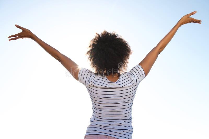 Молодая женщина стоя outdoors против неба при ее поднятые руки стоковые изображения rf