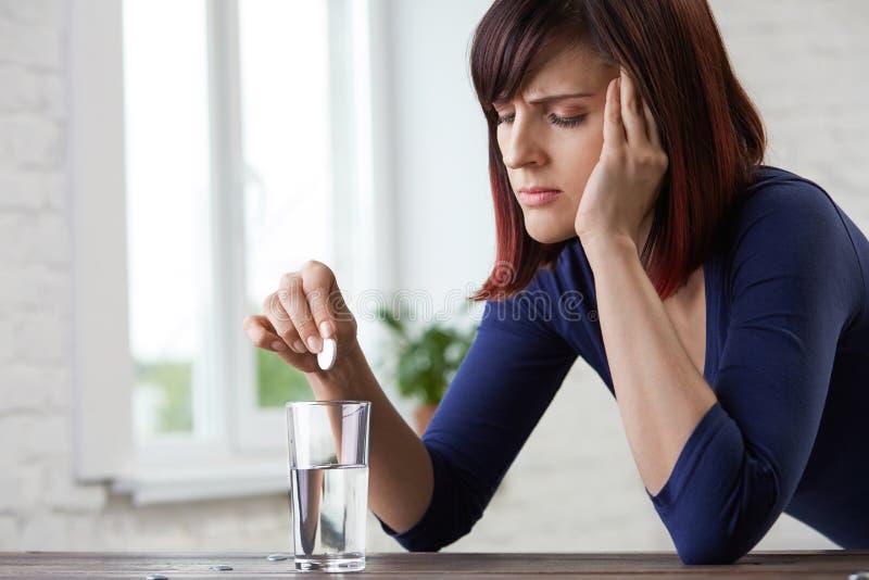 Молодая женщина страдая от сильной головной боли, держащ пальцы к ее вискам и глаза заключения от боли, prepairing для того чтобы стоковые фото