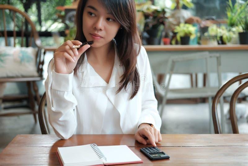 Молодая женщина студента держа с ручкой и думая что-то h стоковые изображения rf