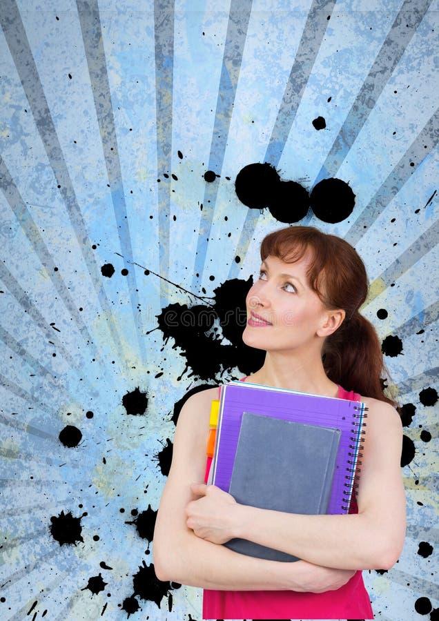 Молодая женщина студента держа тетради против голубой splattered предпосылки стоковая фотография