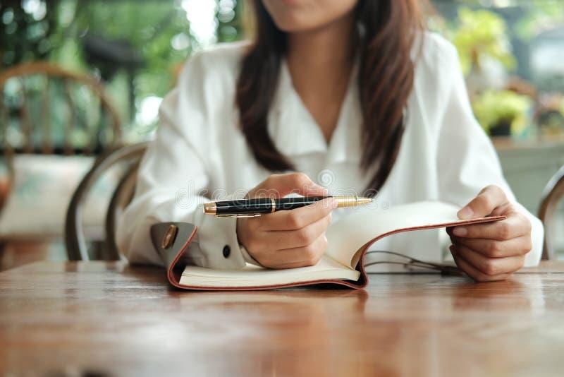 Молодая женщина студента сидя на ручке удерживания библиотеки и сочинительстве o стоковые фотографии rf