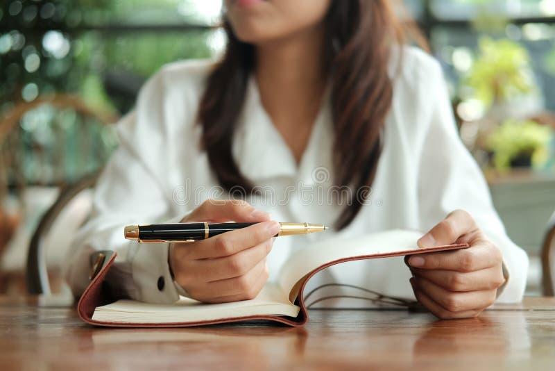 Молодая женщина студента сидя на ручке удерживания библиотеки и сочинительстве o стоковая фотография rf