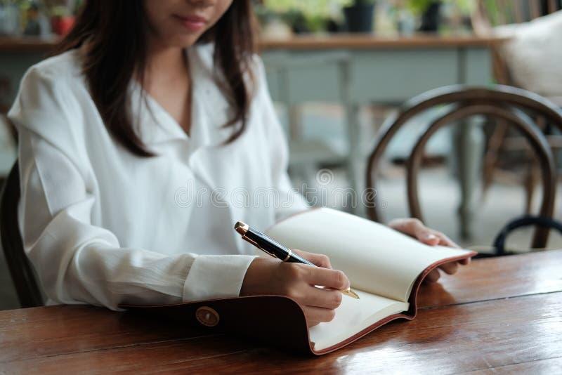 Молодая женщина студента сидя на ручке удерживания библиотеки и сочинительстве o стоковая фотография