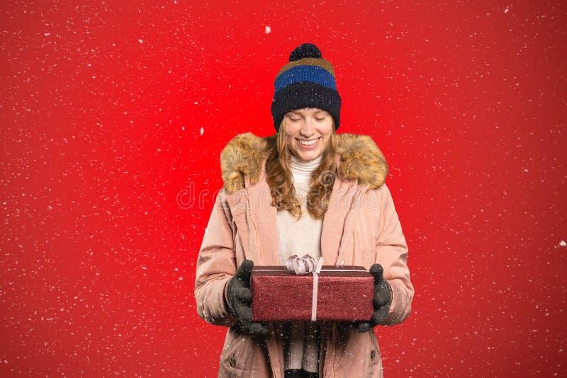 Молодая женщина счастливо держит подарок на Рождество в своей руке и снег стоковая фотография