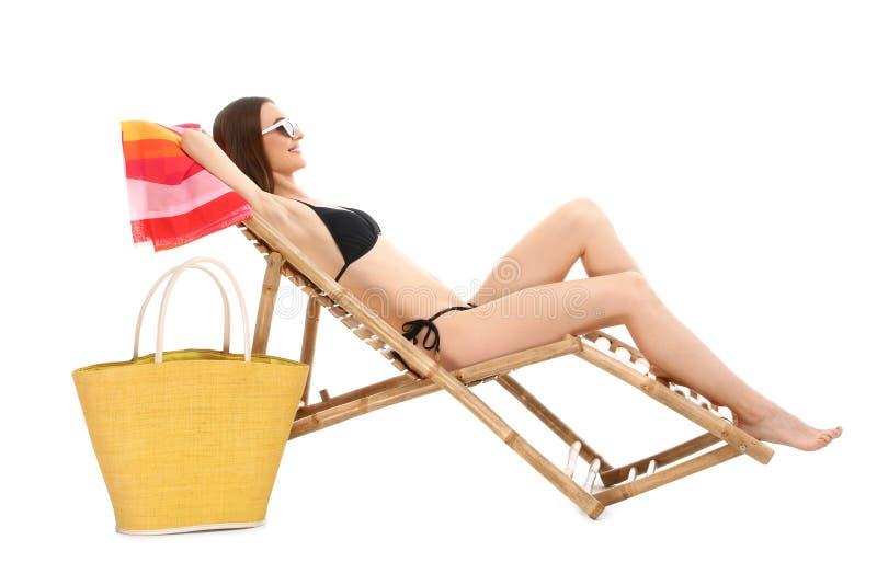 Молодая женщина с аксессуарами пляжа на солнце против белой предпосылки стоковое изображение rf