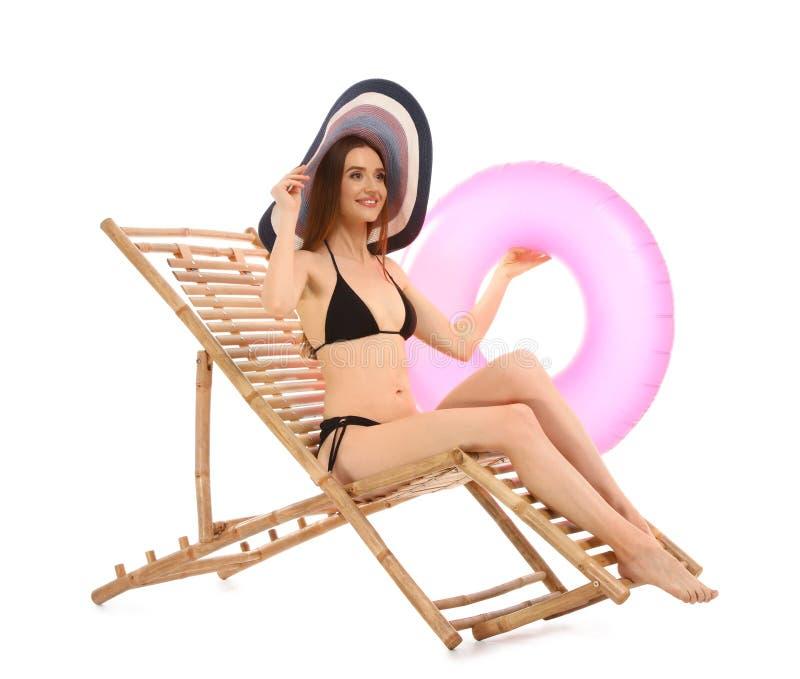Молодая женщина с аксессуарами пляжа на шезлонге против белизны стоковая фотография