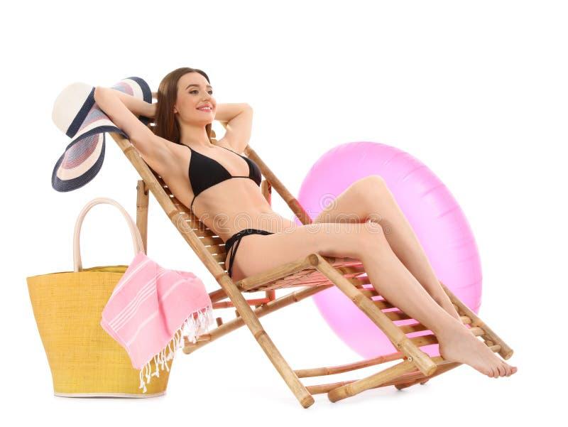Молодая женщина с аксессуарами пляжа на шезлонге против белизны стоковые изображения rf