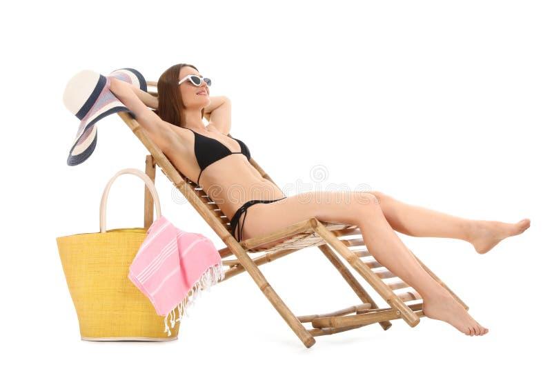 Молодая женщина с аксессуарами пляжа на шезлонге против белизны стоковая фотография rf