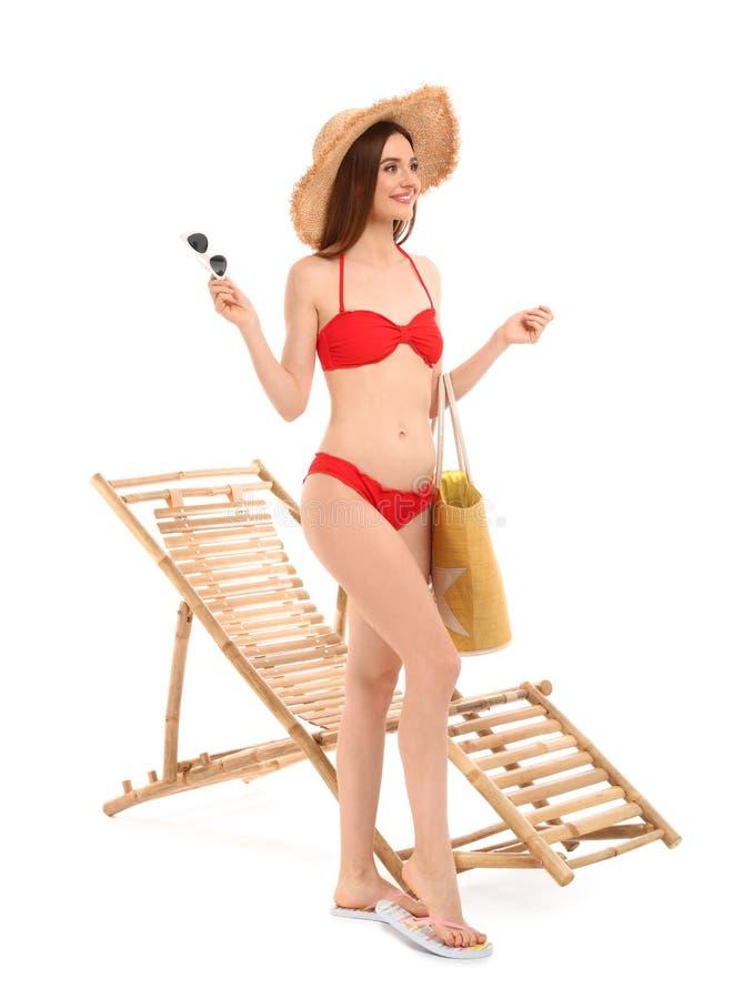 Молодая женщина с аксессуарами пляжа около шезлонга против белизны стоковая фотография