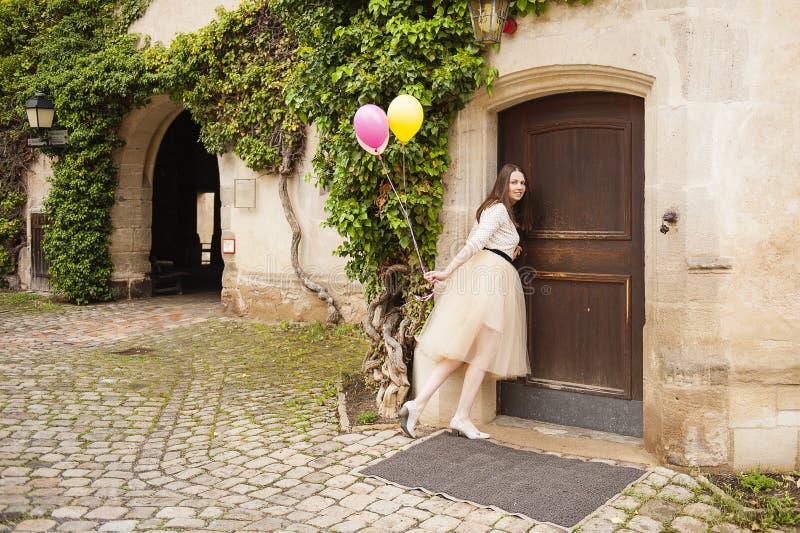 Молодая женщина с воздушными шарами раскрывает дверь стоковое изображение