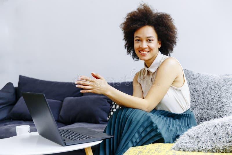 Молодая женщина с вьющиеся волосы, компьтер-книжкой польз и сидеть на sof стоковое фото