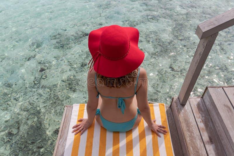 Молодая женщина с голубым бикини и красной шляпой на полотенце над кристально ясным открытым морем стоковое изображение rf