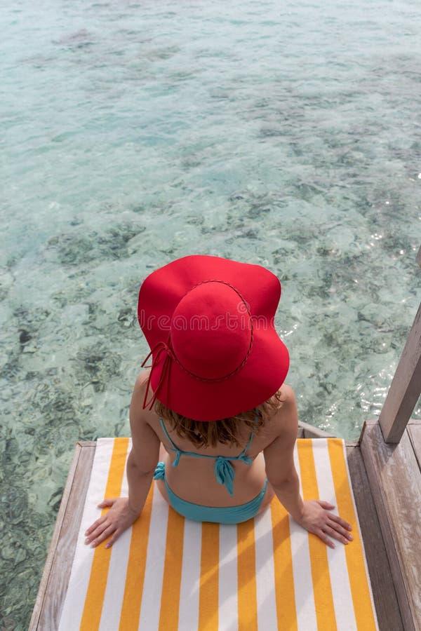 Молодая женщина с голубым бикини и красной шляпой на полотенце над кристально ясным открытым морем стоковая фотография rf