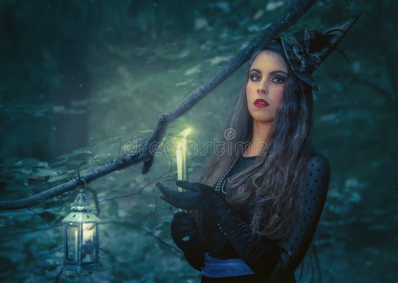 Молодая женщина с горящей книгой в лесе стоковое изображение