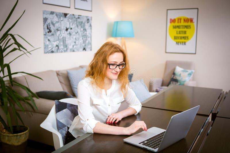 Молодая женщина с длинными красными волосами и стеклами для работ взгляда, печатей на серой клавиатуре компьтер-книжки сидя на де стоковая фотография rf