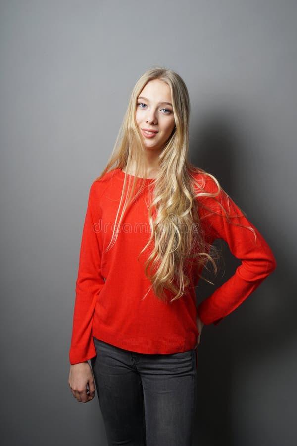 Молодая женщина с длинными светлыми волосами стоя против серой стены стоковое фото rf