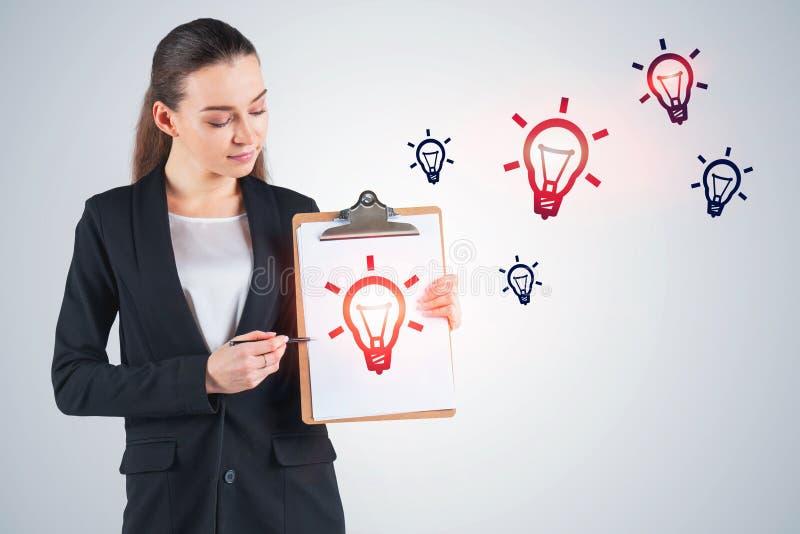 Молодая женщина с доской сзажимом для бумаги, электрическими лампочками стоковые изображения