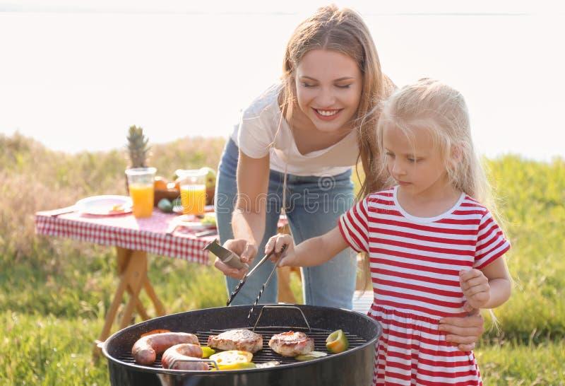 Молодая женщина с дочерью варя мясо, сосиски и овощи на гриле барбекю outdoors стоковые фото