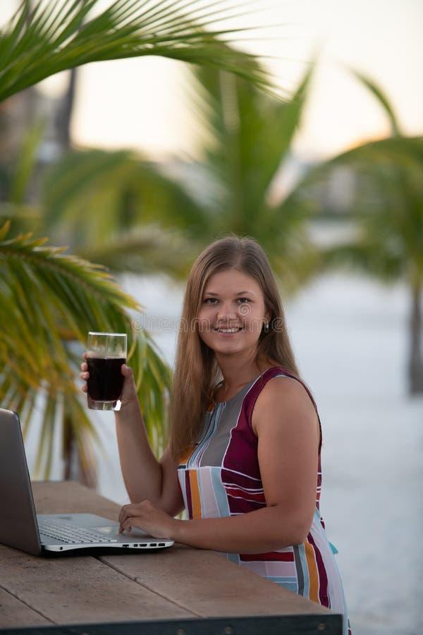 Молодая женщина с компьютером перед ладонью стоковое фото