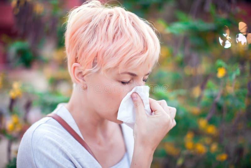 Молодая женщина с короткими волосами чихая в ткань грипп, аллергия, жидкий нос r стоковое изображение