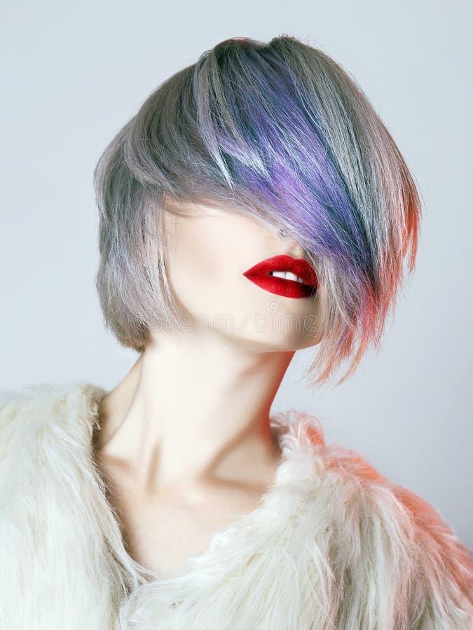 Молодая женщина с красочными волосами, белым мехом стоковая фотография