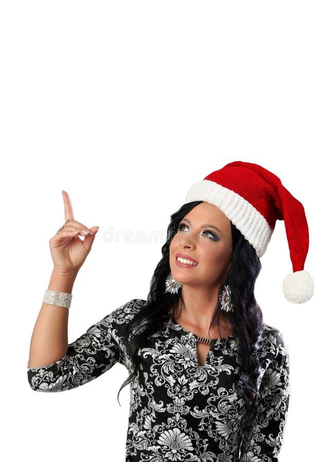 Молодая женщина с крышкой Санта показывая что-то Дама пункт стоковые фотографии rf