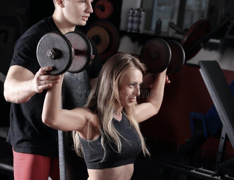 Молодая женщина с личным тренером работая на имитаторе в спортзале стоковое фото rf
