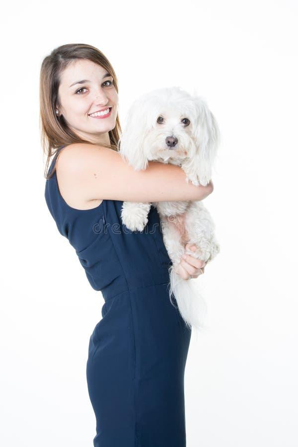 Молодая женщина с маленькой собакой в оружиях на белой предпосылке стоковое изображение