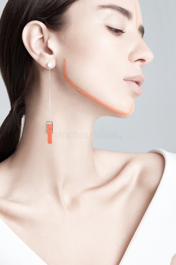Молодая женщина с оранжевыми линиями краски на стороне стоковое фото