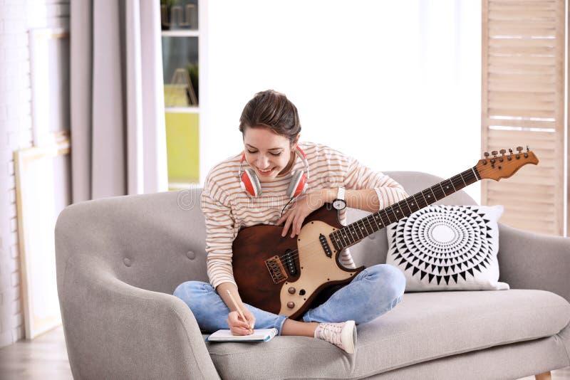 Молодая женщина с песней электрической гитары составляя стоковые фотографии rf