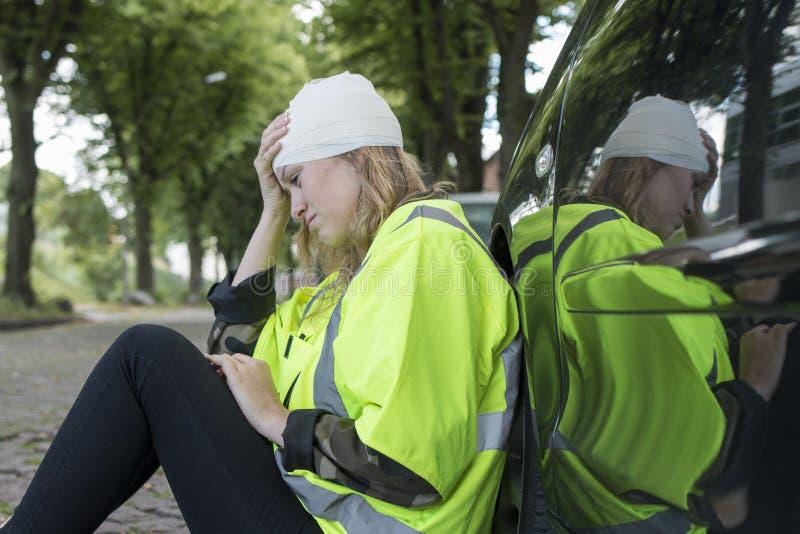 Молодая женщина с повреждением головы полагается против автомобиля стоковое изображение rf