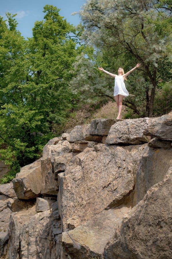 Молодая женщина с поднятым небом рук на краю скалы в su стоковые изображения rf