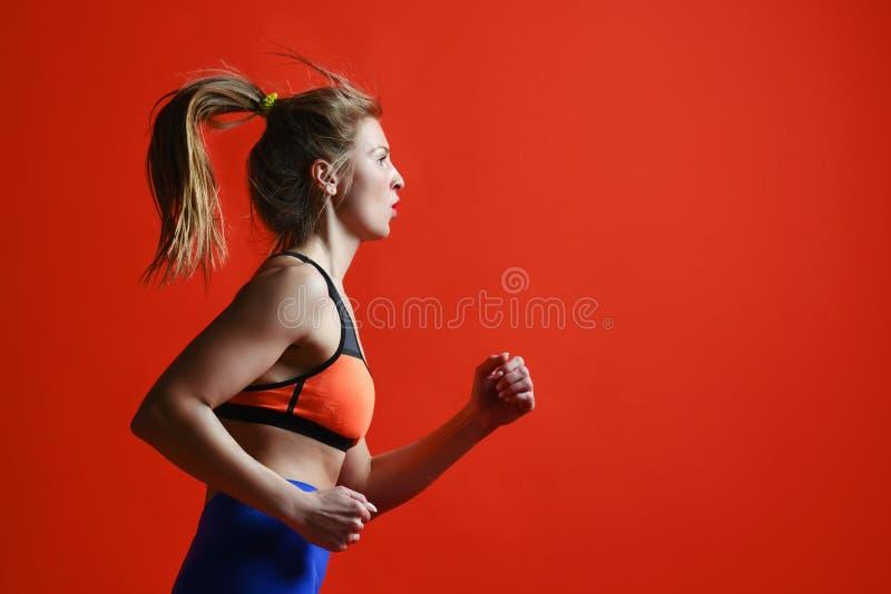Молодая женщина с подходящие скакать и ходом тела против красной предпосылки стоковые изображения