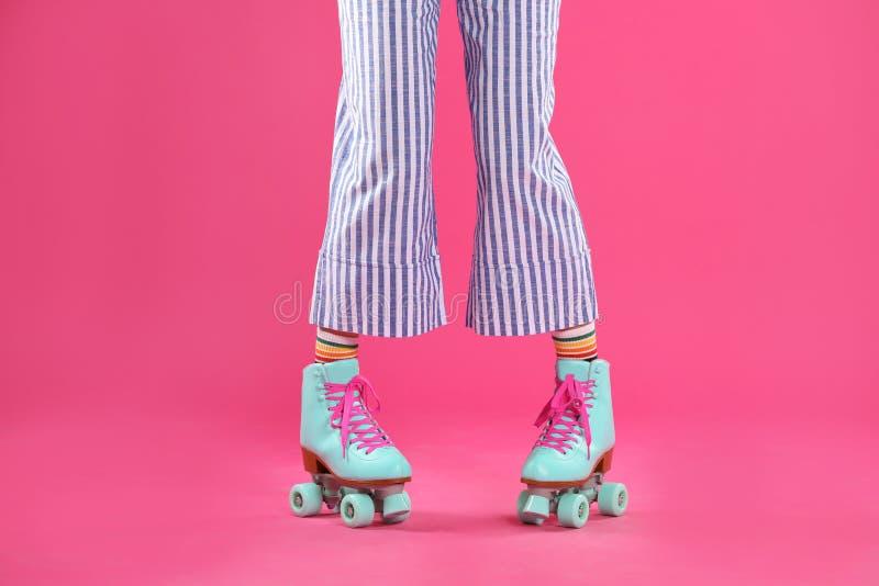 Молодая женщина с ретро коньками ролика на предпосылке цвета стоковое изображение