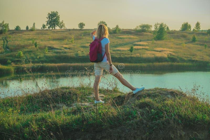 Молодая женщина с розовым рюкзаком стоит на голубом конце предпосылки карьеров мела вверх во времени захода солнца стоковая фотография rf